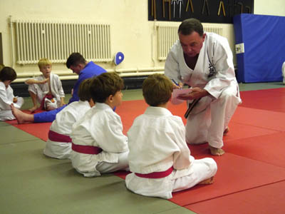 Sensei Frank Perry speaks to the Judo class kids before they show their skills in action.
